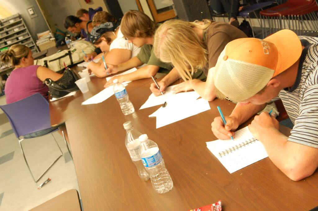 Group of youth writing