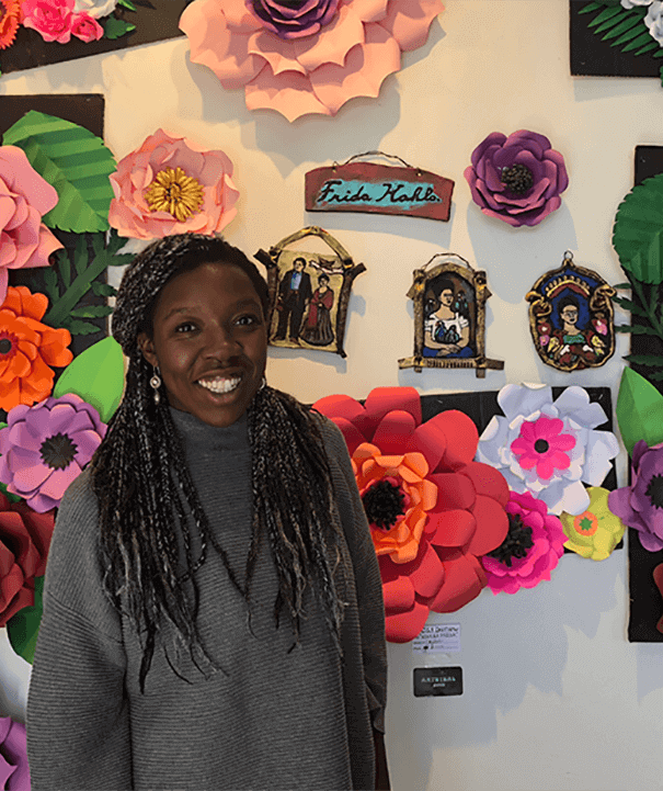 Adriel Long in front of wall of art and flowers